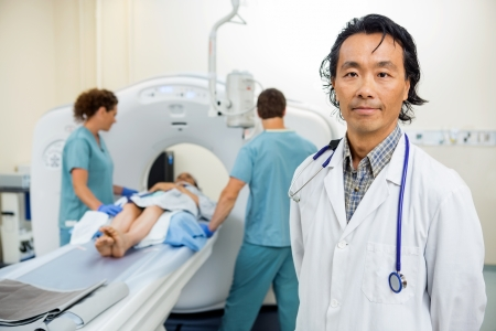 tomography: Portrait of male radiologist with nurses preparing patient for CT scan test in hospital