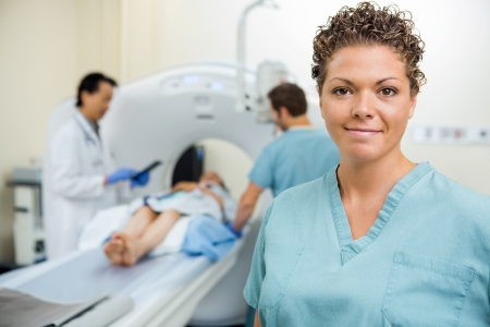 medical scanner: Portrait of mid adult nurse with doctor and colleague preparing patient for CT scan in hospital Stock Photo