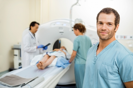 radiologist: Portrait of male nurse with colleague and radiologist preparing patient for CT scan in examination room