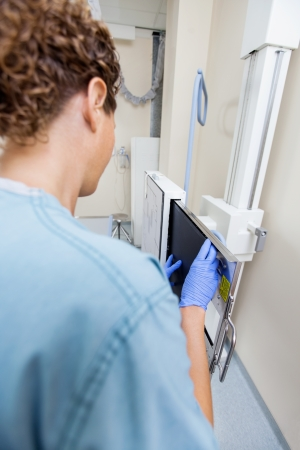 Rear view of mid adult nurse adjusting xray film in machine at examination room photo