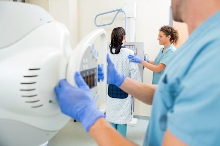 lab tech: Male nurse adjusting xray machine with colleague and patient in examination room Stock Photo