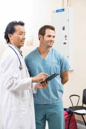 Male nurse and radiologist with digital tablet in examination room photo