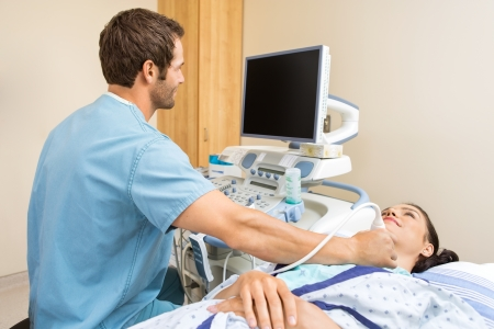 Male nurse performing ultrasound on young patients neck in examination room Stock Photo
