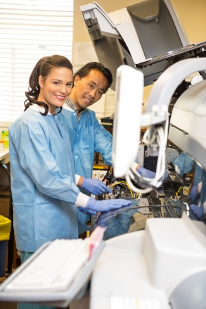 lab tech: Portrait of multiethnic researchers smiling while working together in laboratory