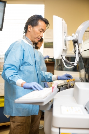 research facilities: Mature male researcher loading specimens in chemical analyzer