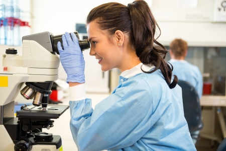 Side view of female scientist using microscope in laboratory photo
