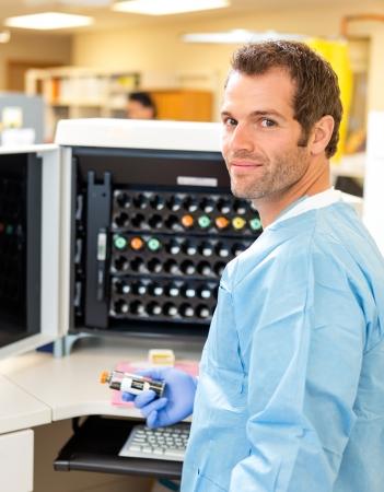 hematology: Side view portrait of lab tech holding sample by hematology analyzer