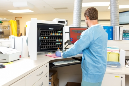 lab tech: Rear view of male lab tech performing hematology analysis in hospital lab