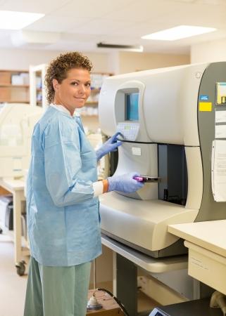 coagulation: Portrait of mid adult female medical lab tech loading specimen for coagulation test analysis