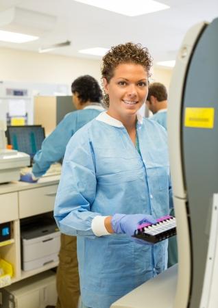 coagulation: Portrait of happy female medical lab tech with sample for coagulation analysis