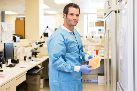 Portrait of lab tech standing in lab holding bag of frozen plasma photo