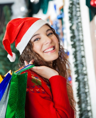Portrait of beautiful young woman in Santa hat carrying shopping bags at Christmas store photo