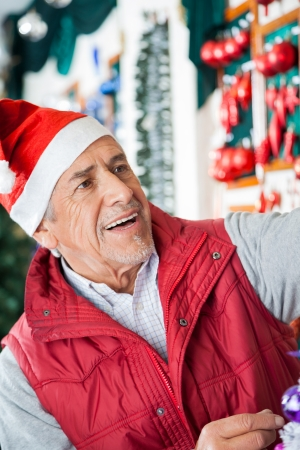 Senior male owner in Santa hat working at Christmas store photo