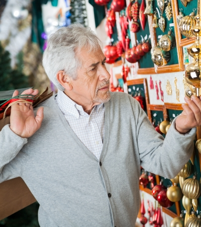 Senior man with shopping bags buying Christmas ornaments at store photo