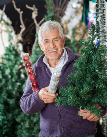 Portrait of happy senior man holding at Christmas tree and baubles in store photo