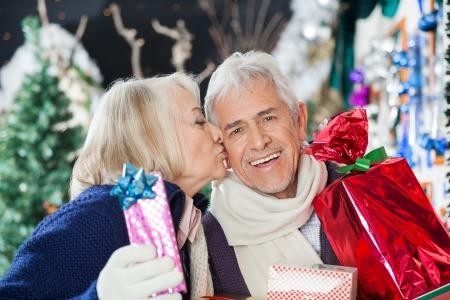 Loving senior woman kissing man with Christmas presents at store photo