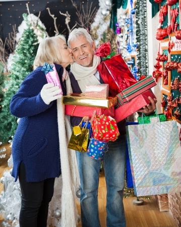 Side view of senior woman kissing man with stacked Christmas presents at store photo