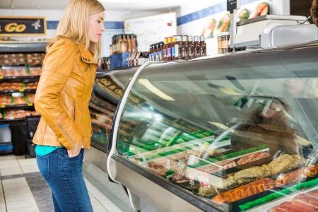Carnicería: Vista lateral de la carne de la selección femenina de clientes en la tienda del carnicero