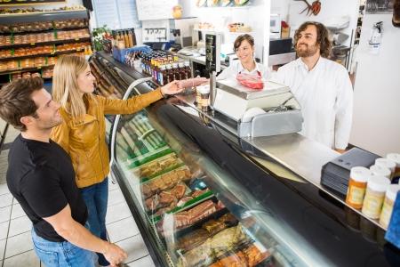 Carnicería: Pareja de comprar carne de vendedor en el contador en la carnicería