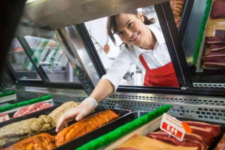 Portrait of smiling saleswoman picking meat displayed in cabinet at butchers shop