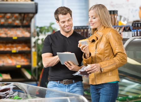 checking ingredients: Couple using digital tablet while checking ingredients of product at butchers shop Stock Photo