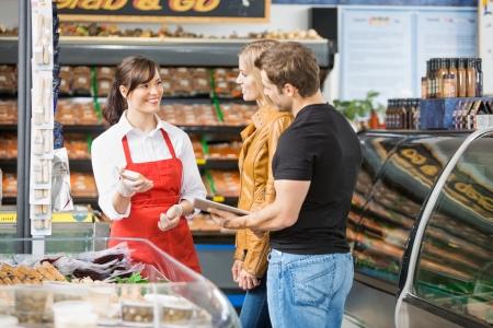 the clerk: Dependienta sonriente ayudando pareja en la compra de carne en la carnicer�a Foto de archivo