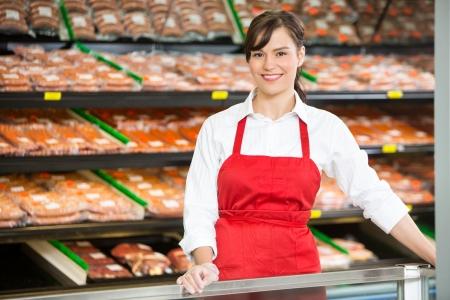 Ritratto di bella commessa sorridente, mentre in piedi al bancone nel negozio di macelleria Archivio Fotografico - 25336521