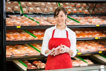 Portrait of happy saleswoman holding meat packages at counter in butchers shop