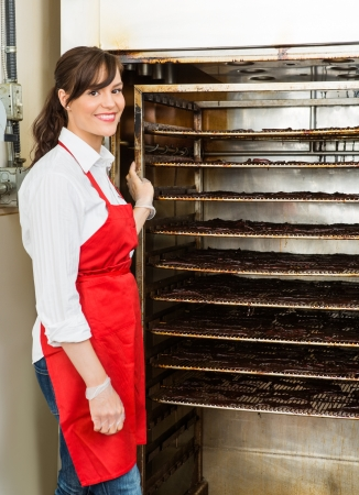 dehydrated: Portrait of beautiful butcher standing by beef jerky smoker