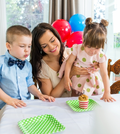 Mother and children celebrating birthday with cupcake on table photo