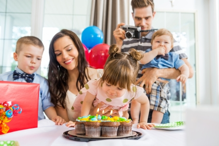 birthday adult: Family watching girl blowing out candles on birthday cake at home