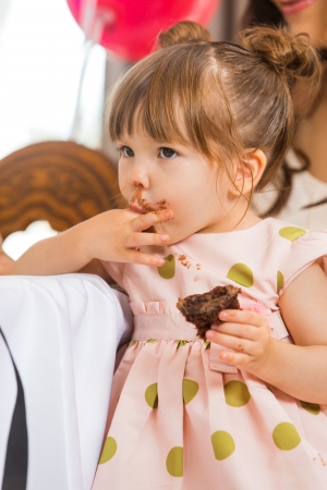 finger licking: Cute birthday girl eating cake with icing on her face at home Stock Photo