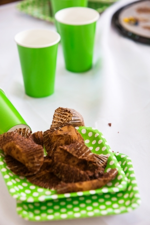 paper plates: Used cupcake wrappers and disposable cups at birthday party