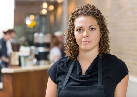 Portrait of beautiful mid adult female owner at espresso bar photo