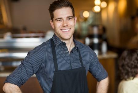 empleadas: Retrato de feliz joven macho due�o de pie en la cafeter�a