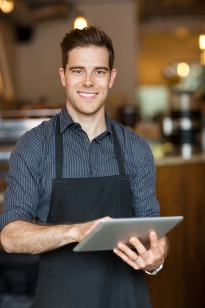 coffeeshop: Portrait of happy male owner holding digital tablet while standing in cafe