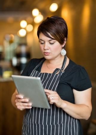 Beautiful female owner using digital tablet in coffee shop photo