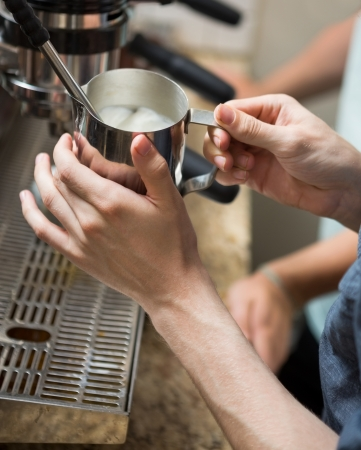 Cropped image of barista steaming milk in coffeeshop photo