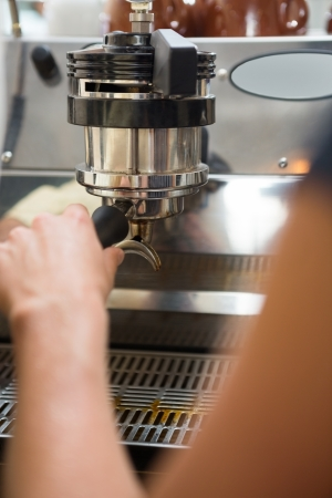 Cropped image of barista with portafilter making coffee photo
