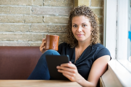 Portrait of woman with coffee mug and digital tablet sitting by window in cafe photo