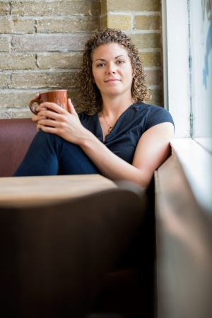 Portrait of beautiful woman holding coffee cup in cafeteria photo
