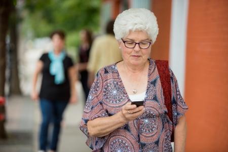 ancianos caminando: Mujer mayor de mensajes de texto en teléfonos inteligentes al aire libre
