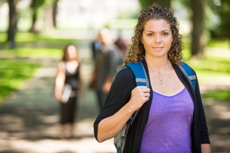waistup: Portrait of confident female grad student with backpack standing at campus with friends in background Stock Photo