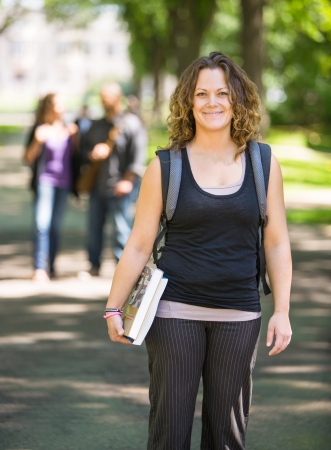 mid adult female: Portrait of mid adult female student with backpack and book standing on campus road Stock Photo