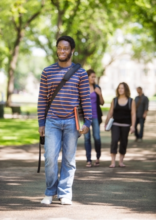 Full length of smiling male student walking on campus road with friends in background photo