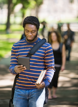 Young male student using digital tablet on campus with friends in background photo