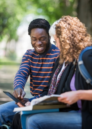 Happy African American university student using digital tablet with friends on campus photo