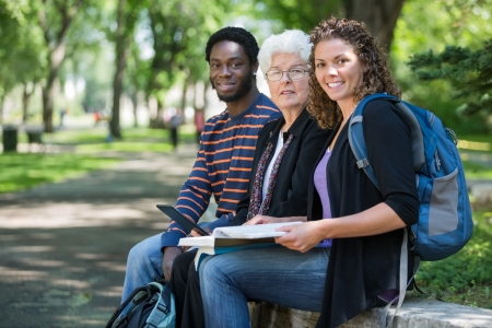 Portrait of confident multiethnic university students sitting on parapet at campus photo