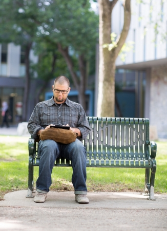 man front view: Male university student using digital tablet on bench at campus Stock Photo