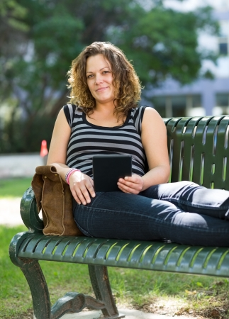 Portrait of confident university student with digital tablet sitting on bench at campus photo